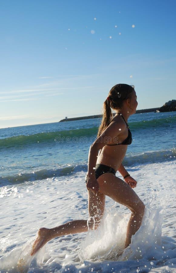 Jeune fille exécutant dans la vague déferlante. photo libre de droits