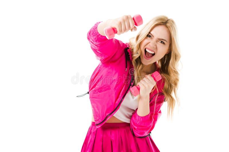 Jeune fille féroce s'exerçant avec les haltères roses photographie stock libre de droits