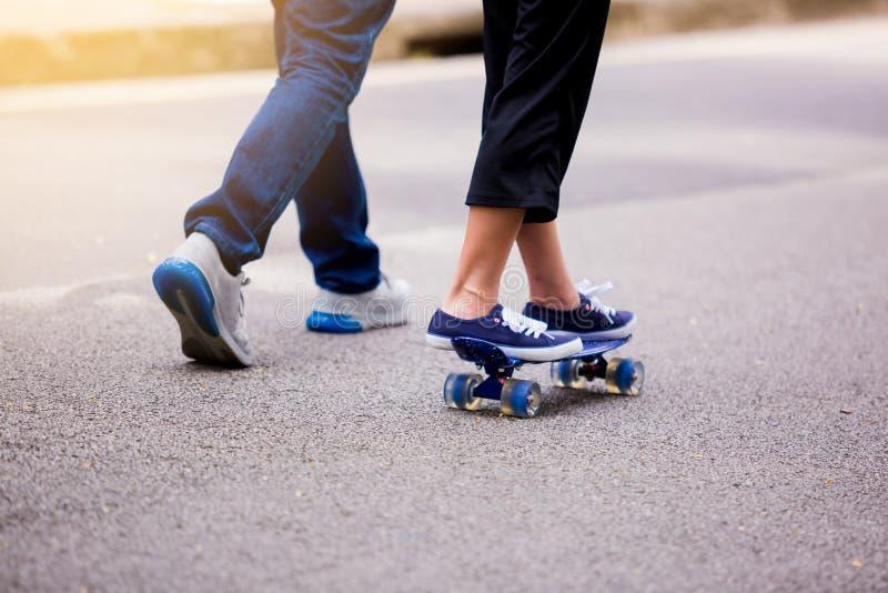 Jeune fille faisant de la planche à roulettes avec son papa courant au parc I extérieur photos stock
