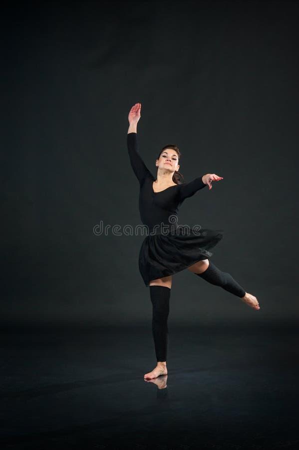 Jeune fille faisant des exercices gymnastiques sur le fond noir de studio images stock