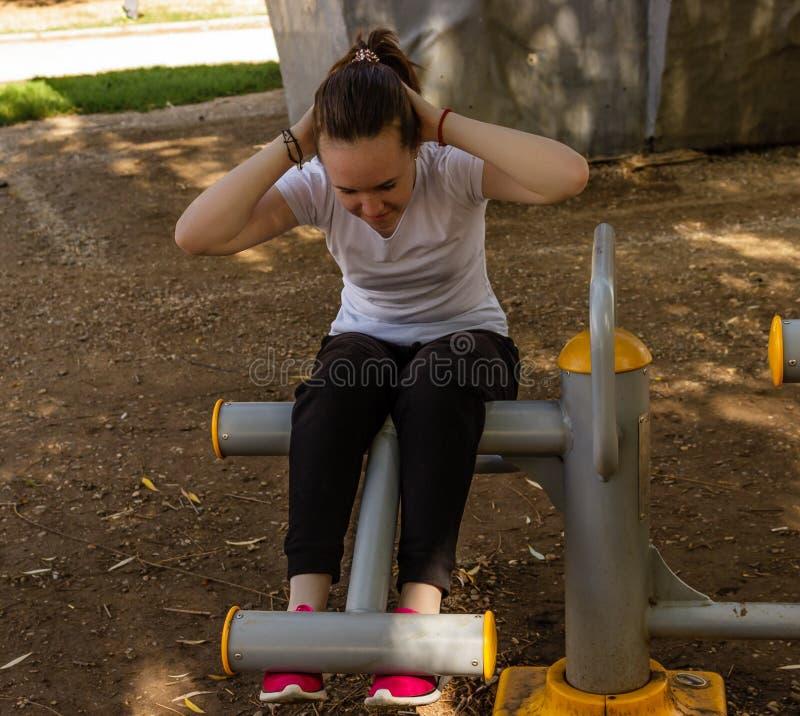 Jeune fille faisant des exercices pour des muscles abdominaux image stock