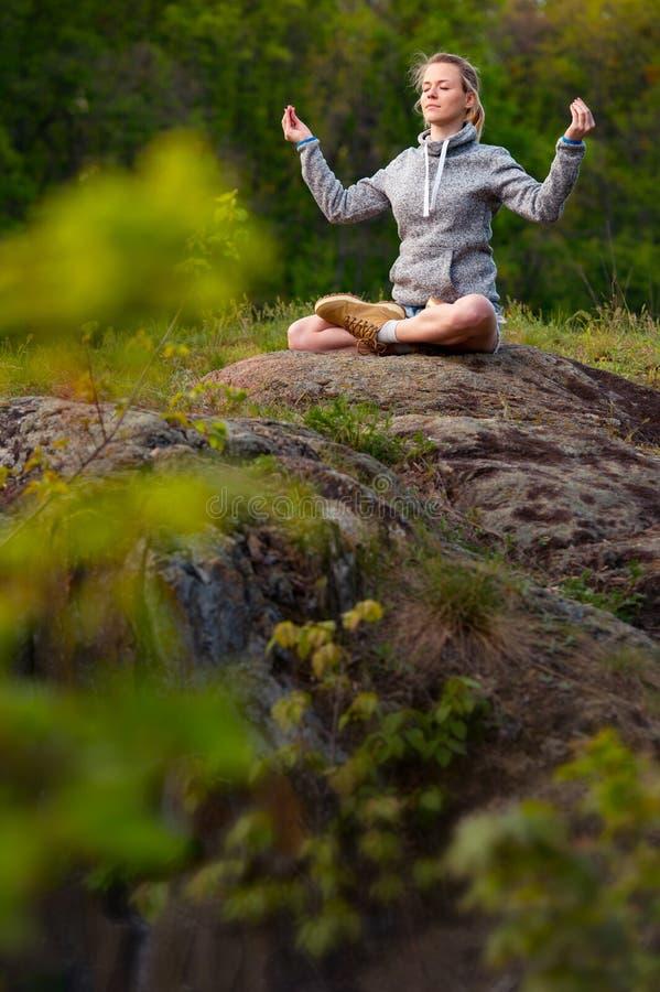 Jeune fille faisant l'exercice de forme physique de yoga extérieur dans le beau résumé image libre de droits