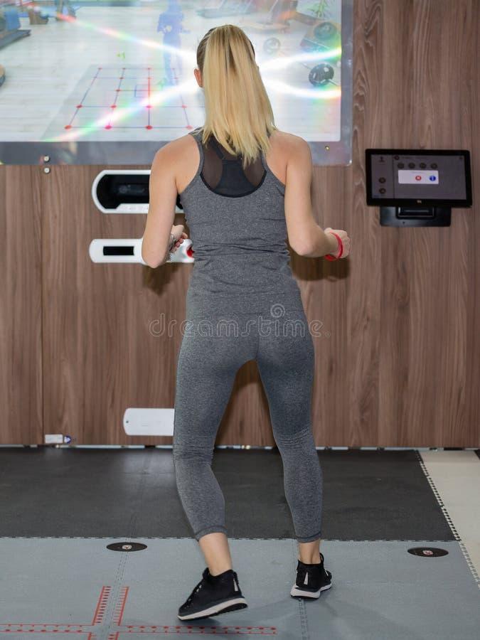 Jeune fille faisant la forme physique sur un tapis spécial de technologie avec l'écran accrochant sur le mur photographie stock libre de droits