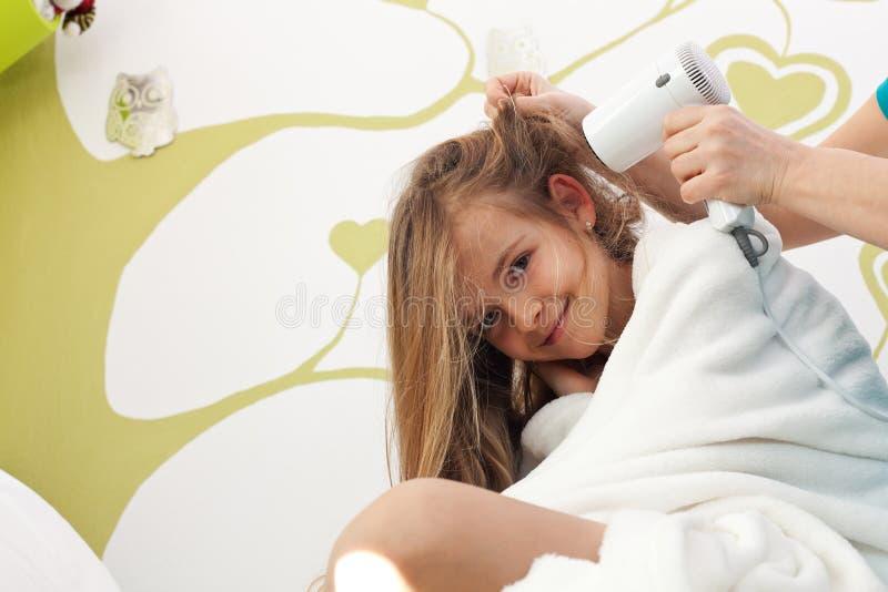 Jeune fille faisant sécher ses cheveux après bain images stock