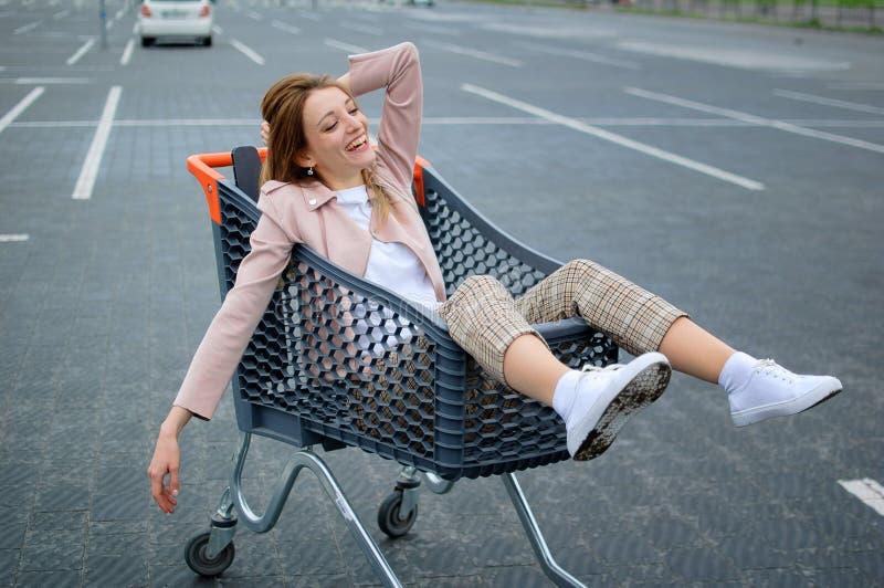 Jeune fille folle dans les vêtements sport et des chaussures blanches d'espadrille dans le stationnement de supermarché ayant l'a photo libre de droits