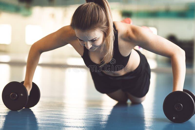 Jeune fille forte faisant des pousées sur des haltères dans le gymnase image stock