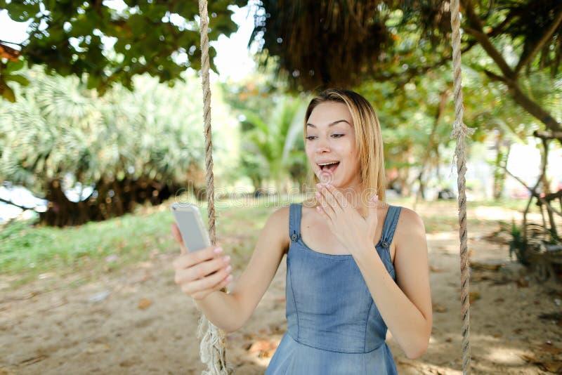 Jeune fille gaie à l'aide du smartphone et mettant en oeuvre les réseaux sociaux, oscillation de monte sur le sable image stock