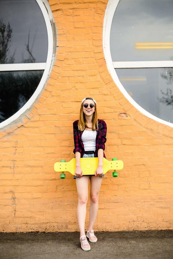 Jeune fille gaie posant avec la planche à roulettes jaune contre le mur orange photo libre de droits