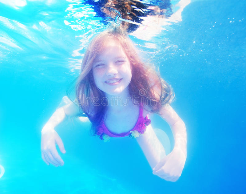 Jeune fille heureuse avec l'eau du fond aux cheveux longs dans la piscine photo stock