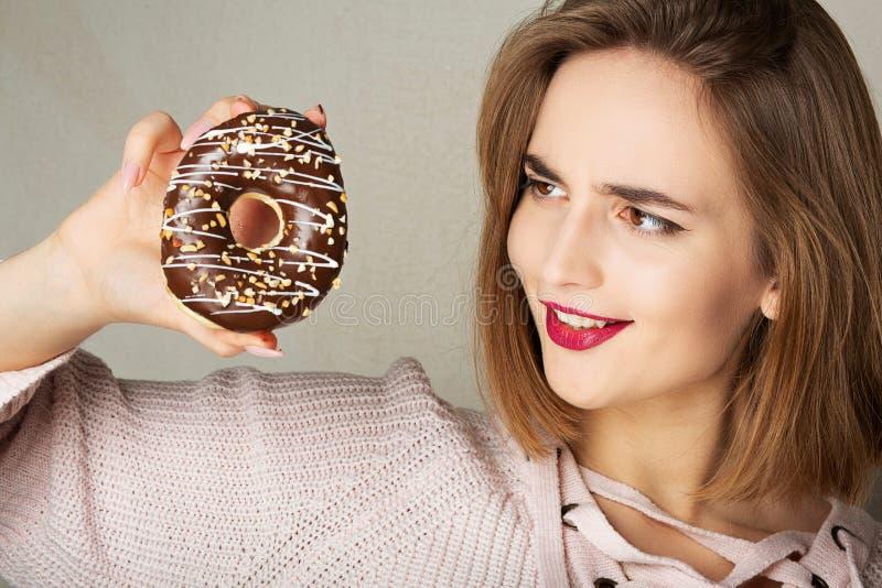 Jeune fille heureuse avec les lèvres roses tenant le beignet de chocolat au-dessus d'un fond gris photos libres de droits