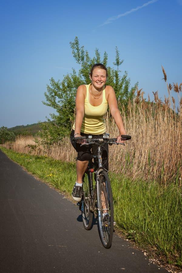 Jeune fille heureuse avec un vélo image stock