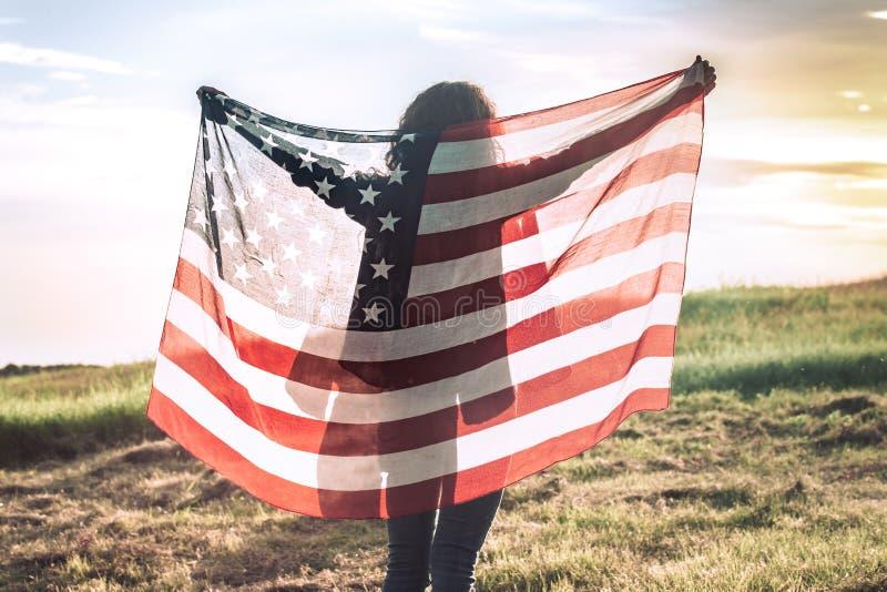 Jeune fille heureuse courant et sautant insouciant avec les bras ouverts au-dessus du champ de blé Tenir le drapeau des Etats-Uni photos libres de droits