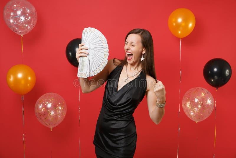 Jeune fille heureuse dans la robe noire criant faisant le geste de gagnant, tenant un bon nombre de paquet de dollars, argent d'a image stock