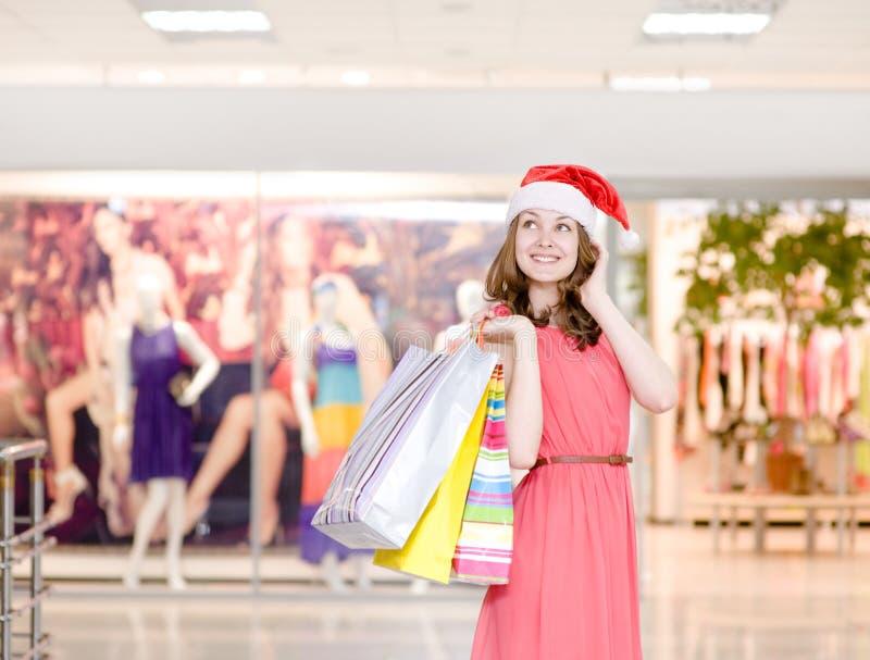 Jeune fille heureuse dans le chapeau de Noël avec des paniers dans les achats photos libres de droits