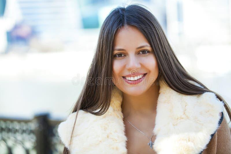 Jeune fille heureuse dans le manteau de peau de mouton sur un fond de la ville images stock