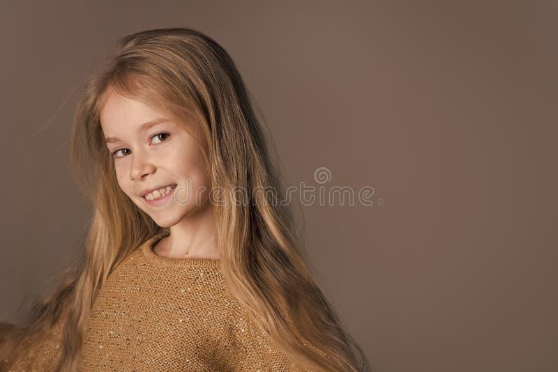 Jeune fille heureuse dans le studio gris, l'espace de copie photos libres de droits