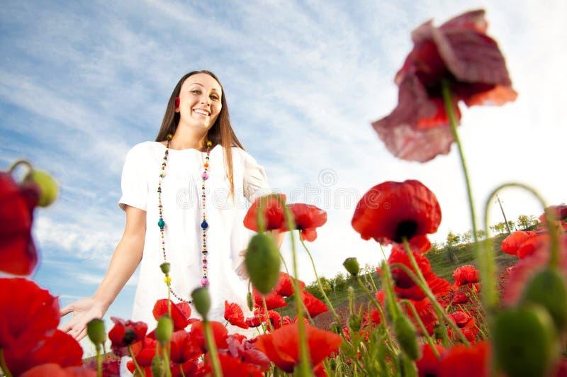Jeune fille heureuse dans les pavots image libre de droits
