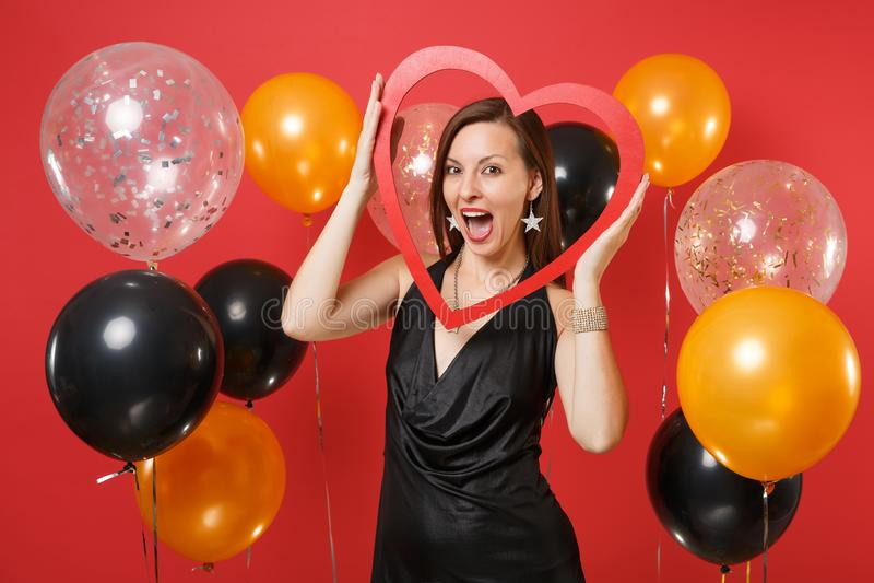 Jeune fille heureuse enthousiaste dans peu de robe noire célébrant tenant le grand coeur en bois rouge sur l'air rouge lumineux d photographie stock