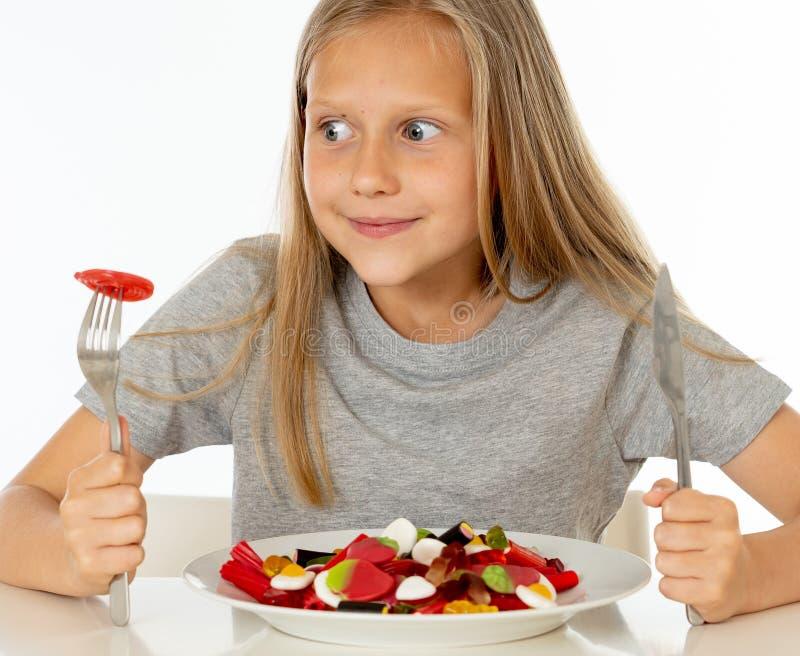 Jeune fille heureuse jugeant un plat plein des sucettes de sucrerie sur le blanc photographie stock libre de droits
