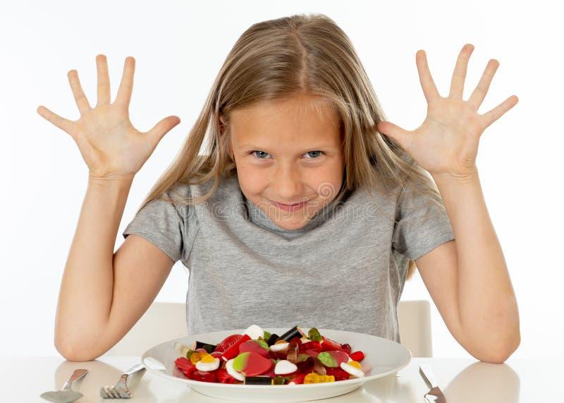 Jeune fille heureuse jugeant un plat plein des sucettes de sucrerie sur le blanc photographie stock