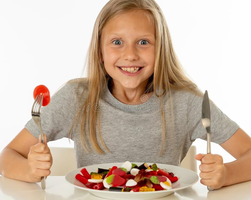 Jeune fille heureuse jugeant un plat plein des sucettes de sucrerie sur le blanc photo stock
