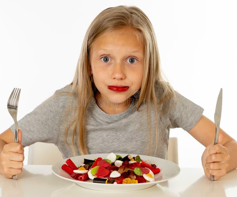 Jeune fille heureuse jugeant un plat plein des sucettes de sucrerie sur le blanc photos stock