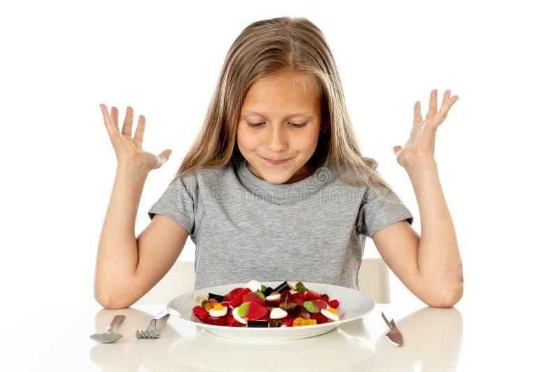 Jeune fille heureuse jugeant un plat plein des sucettes de sucrerie sur le fond blanc photographie stock libre de droits