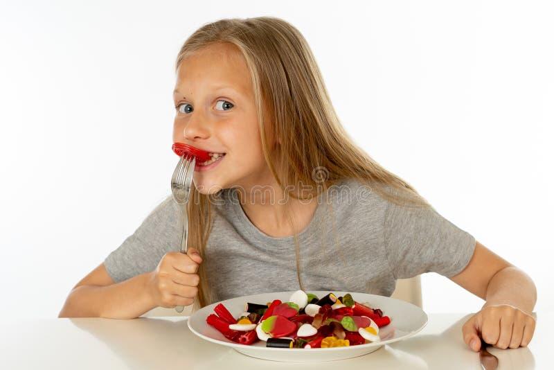 Jeune fille heureuse jugeant un plat plein des sucettes de sucrerie sur le fond blanc photos libres de droits