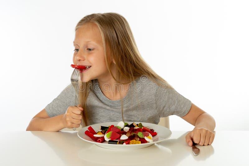 Jeune fille heureuse jugeant un plat plein des sucettes de sucrerie sur le fond blanc photo stock