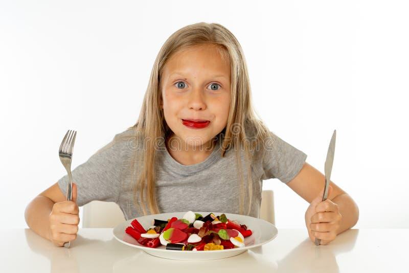 Jeune fille heureuse jugeant un plat plein des sucettes de sucrerie sur le fond blanc photographie stock