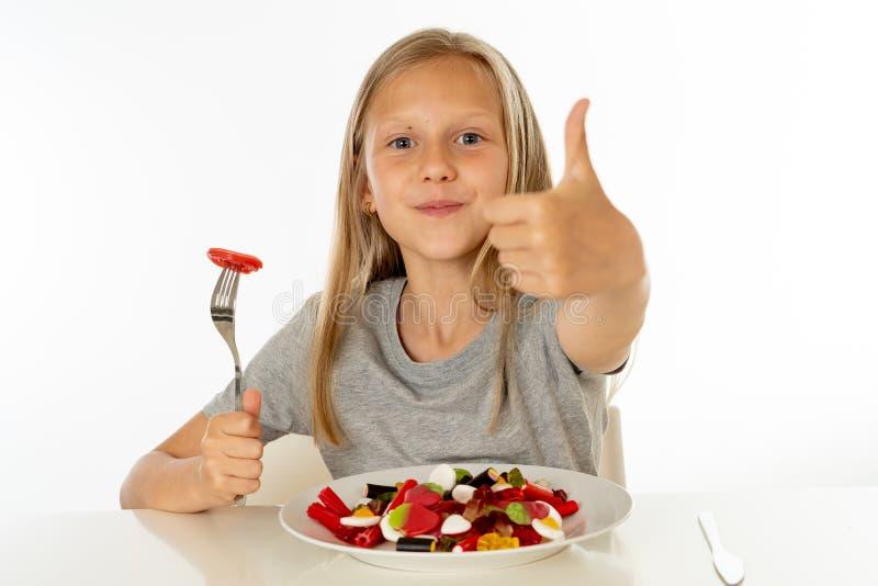 Jeune fille heureuse jugeant un plat plein des sucettes de sucrerie sur le fond blanc images libres de droits