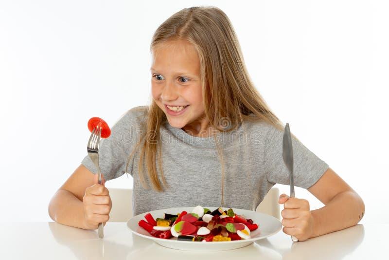 Jeune fille heureuse jugeant un plat plein des sucettes de sucrerie sur le fond blanc image libre de droits