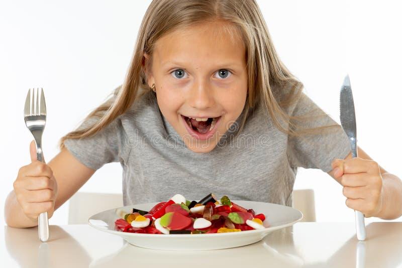 Jeune fille heureuse jugeant un plat plein des sucettes de sucrerie sur le fond blanc image stock