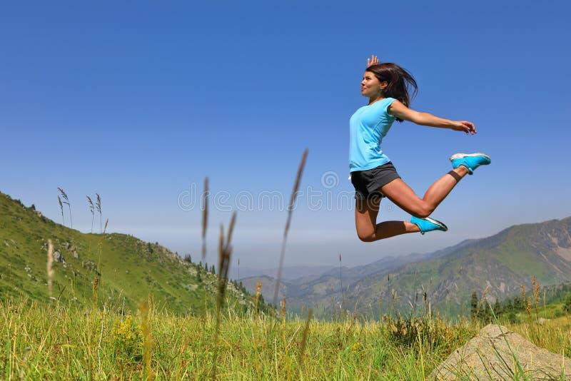 Jeune fille heureuse sautant et appréciant la vie dans le domaine image stock