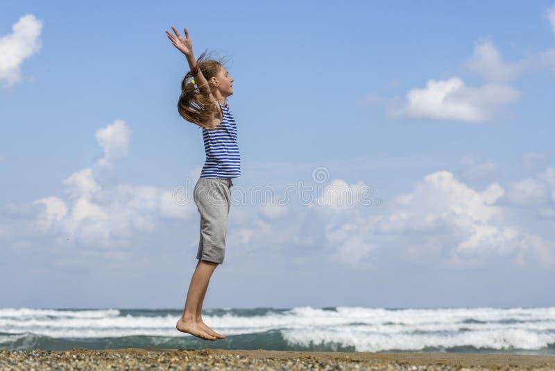 Jeune fille heureuse sautant sur la plage photo stock