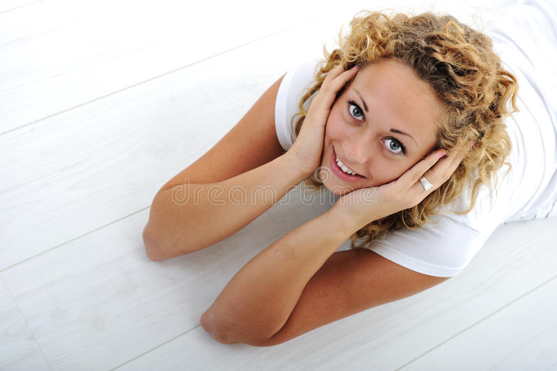 Jeune fille heureuse se trouvant sur l'étage photographie stock
