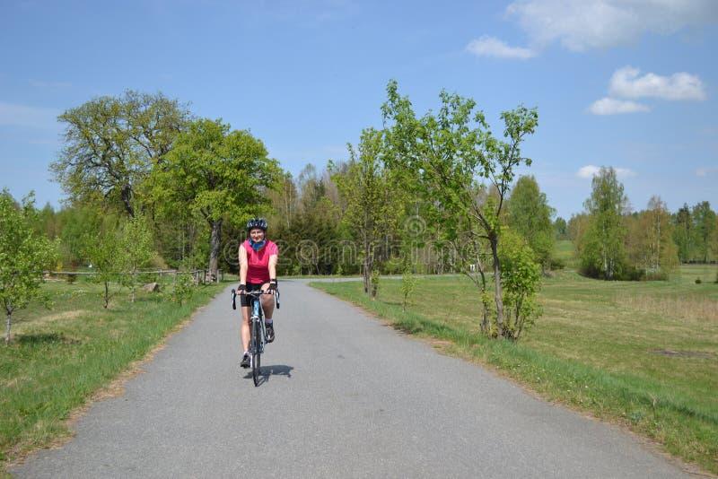 Jeune fille heureuse sur le tour de vélo de ressort image libre de droits