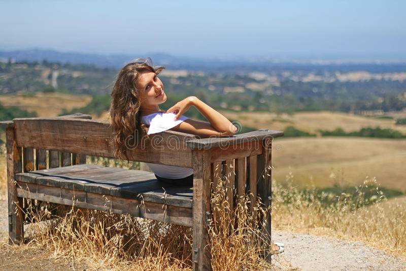 Jeune fille heureuse sur un banc image stock