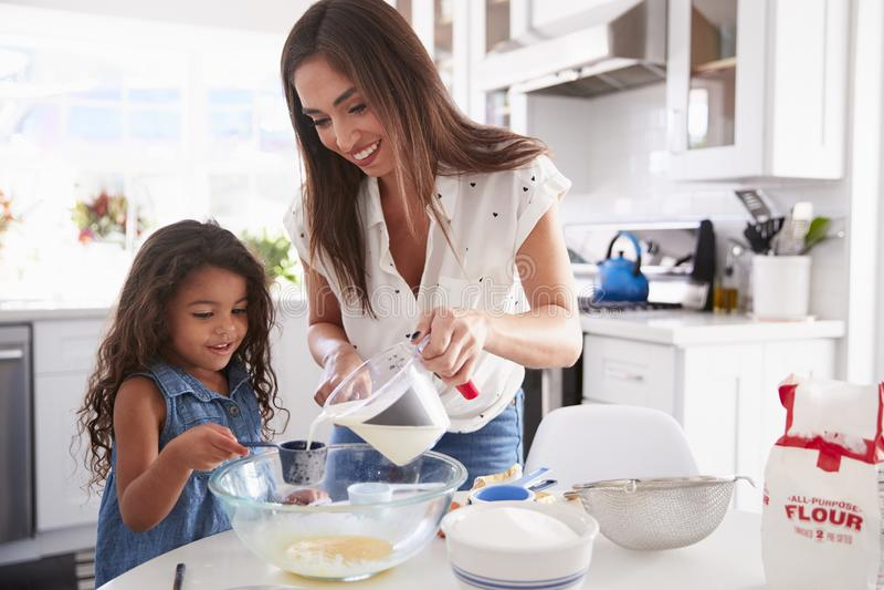 Jeune fille hispanique composant le gâteau dans la cuisine avec l'aide de sa maman, taille image stock