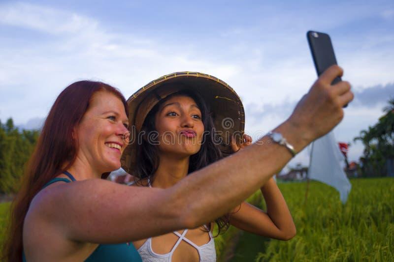 Jeune fille hispanique heureuse et belle dans le chapeau asiatique traditionnel d'agriculteur et la femme caucasienne prenant ? a images stock