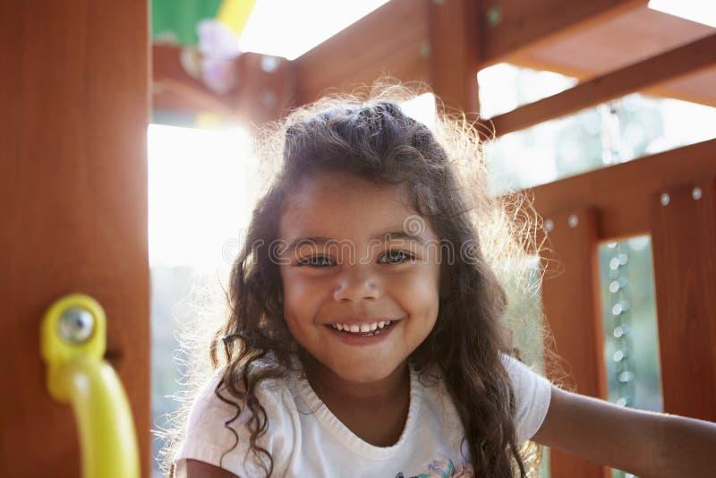 Jeune fille hispanique jouant sur un cadre de s'élever dans un terrain de jeu souriant à la caméra, éclairée à contre-jour, fin  photographie stock libre de droits