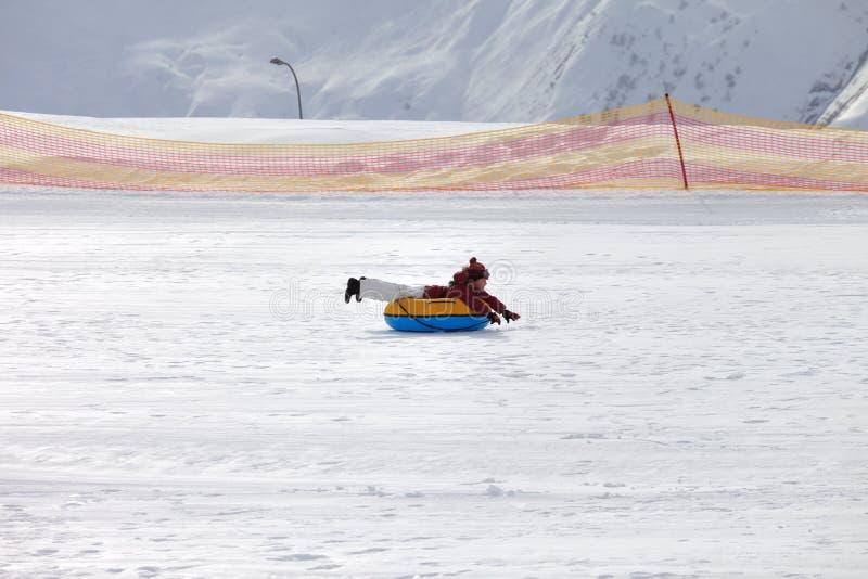 Jeune fille inclinée sur le tube de neige sur la station de sports d'hiver au jour du soleil en montagnes neigeuses photos stock