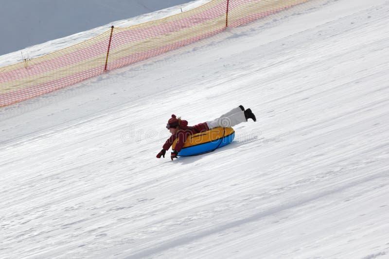Jeune fille inclinée sur le tube de neige sur la station de sports d'hiver au jour d'hiver ensoleillé images libres de droits