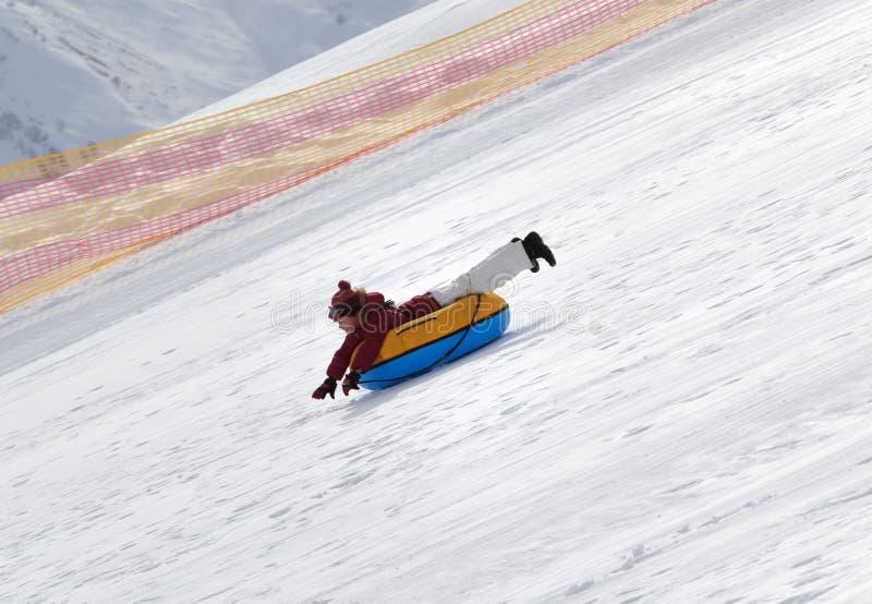 Jeune fille inclinée sur le tube de neige sur la station de sports d'hiver au jour ensoleillé en montagnes neigeuses photographie stock