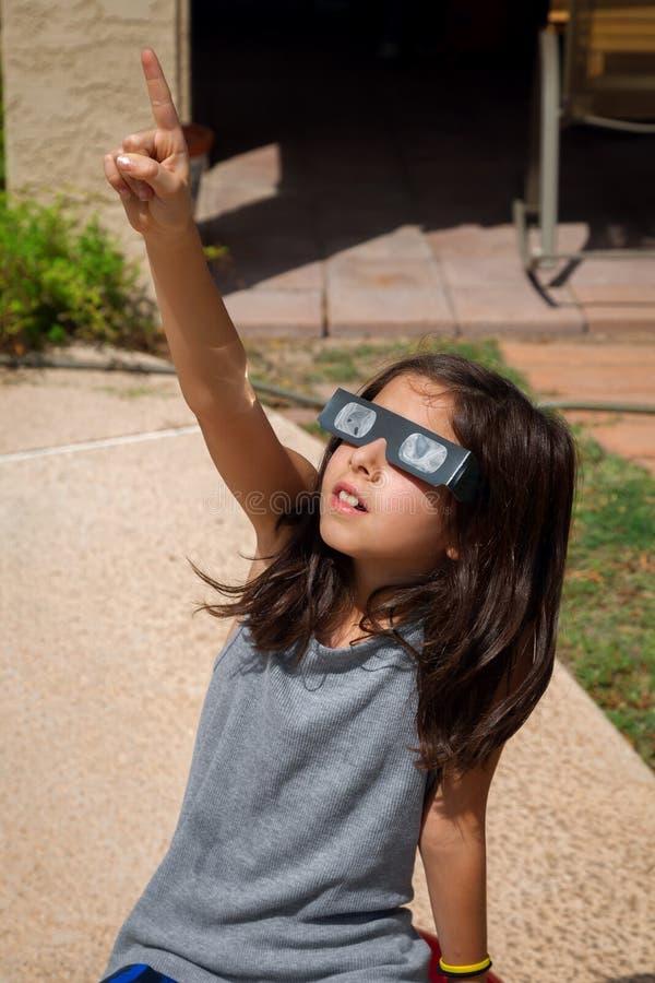 Jeune fille indiquant le ciel tout en portant des lunettes d'éclipse dessus photo stock