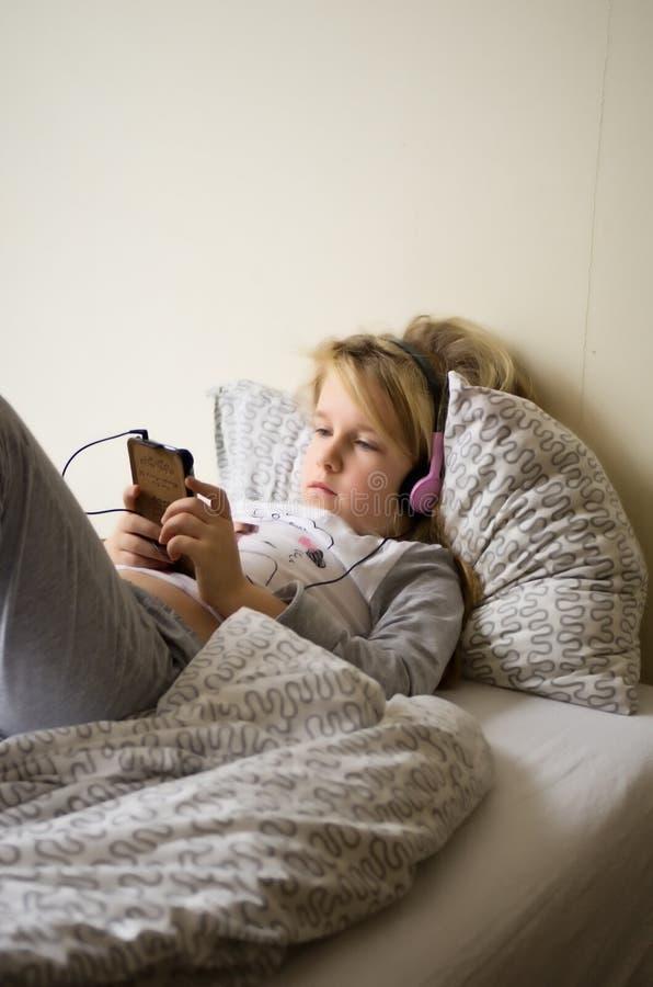 Jeune fille jouant à son téléphone portable dans le lit image stock
