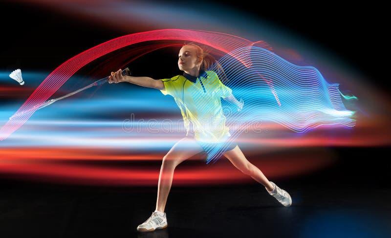 Jeune fille jouant au badminton au-dessus du fond fonc? images stock