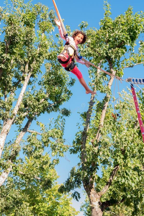 Jeune fille jouant et sautant sur un trempoline images stock