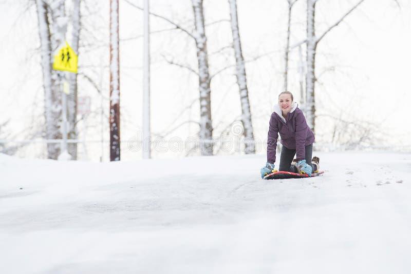 Jeune fille jouant sur un traîneau de neige image stock