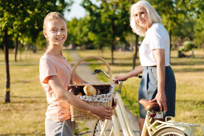 Jeune fille joyeuse allant avoir un pique-nique avec sa grand-mère image libre de droits